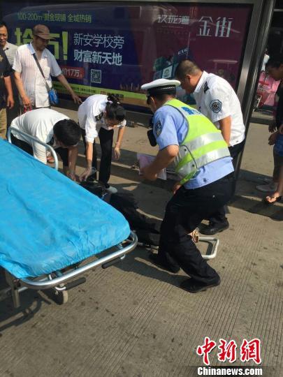 交警协助医护人员将中暑老人抬上救护车。(目击者供图)