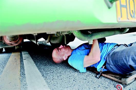 楚天都市报讯 图为:李宏革钻到车底下进行检修左图,出来后T恤已经湿透右图