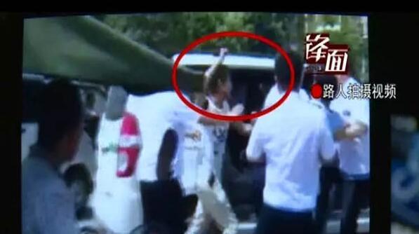 五六名身着白色制服的城管队员围住一名男子推打。