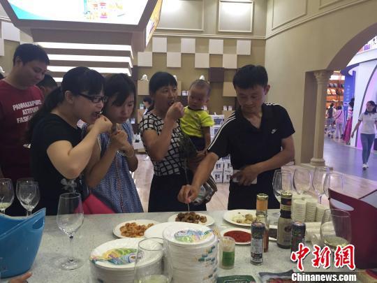 31日,直销中心内的各个馆内试吃活动吸引众多顾客。 吴兰 摄