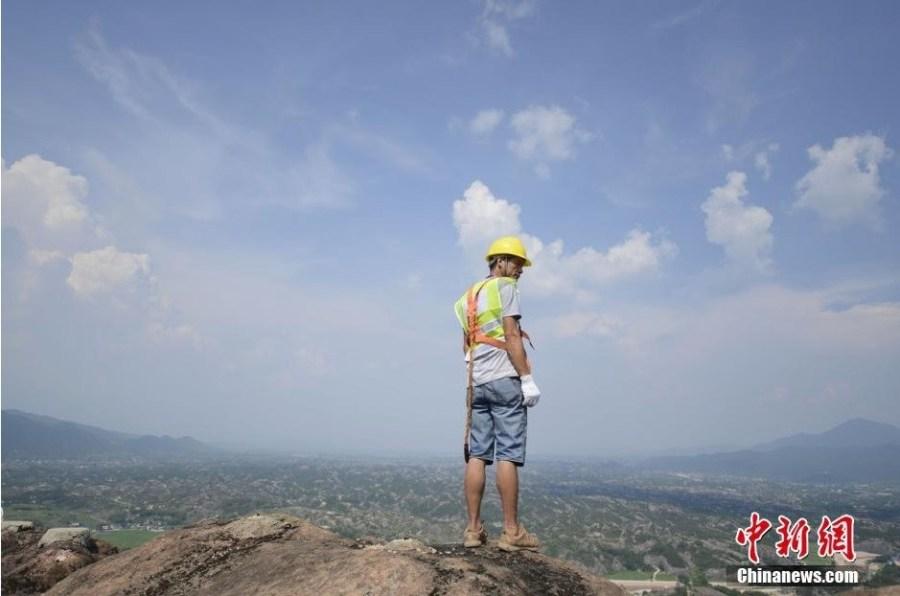 """7月31日,湖南持续高温,平江石牛寨的工人冒着烈日放下速降安全绳,悬吊在百米的悬崖峭壁上进行""""石牛寨""""三个大字的书写工作。图为两位工作配合走下悬崖。"""