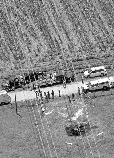 当地时间7月30日,调查人员在热气球起火坠毁事故现场工作