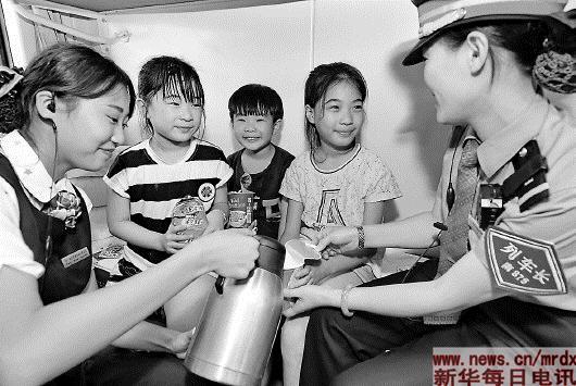 """8月1日,乘务员在福州开往北京的Z60列车上照顾暑期回乡探亲后返程的""""小候鸟""""。暑运以来,南昌铁路局福州客运段为旅客提供热情周到的服务,确保暑期旅客安全出行、方便出行、温馨出行。"""