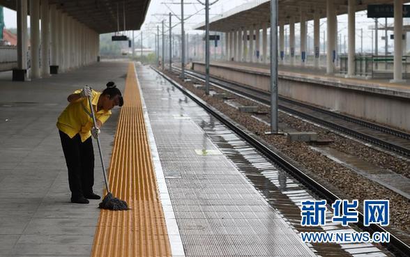 """8月2日,在广西梧州南火车站,一名清洁工人在空无旅客和列车的站台上打扫卫生。当日,受台风""""妮妲""""影响,南广铁路除D3564/7次外所有动车停运,贵广客专开往广州方向的动车除南宁东至贺州6列动车外全部停运,14列途经南宁铁路局管内或始发普速旅客列车停运。 新华社记者 陆波岸"""