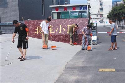 任城区农机局公事员戴着红袖章,正在创卫路段清扫卫生。 图据济宁市任城区民间网站