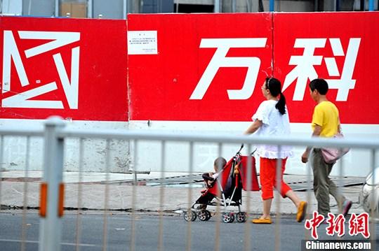 图为福州民众从万科开发的房地产楼盘旁经过。 中新社记者 张斌 摄