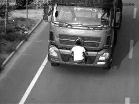 """华商报讯(记者 高羽珑)为逃避交通违法惩罚,有司机选择使用车贴粘住车牌,然而,7月28日,榆林吴堡县沿黄公路一处电子监控设备竟抓拍下令人震惊的一幕,一辆货运车疑为逃避违法惩罚,一名男子竟双手扒在车头车牌前。由于这张照片在网络上意外走红,被网友戏称为史上最""""奇葩""""故意遮挡号牌违法行为。"""