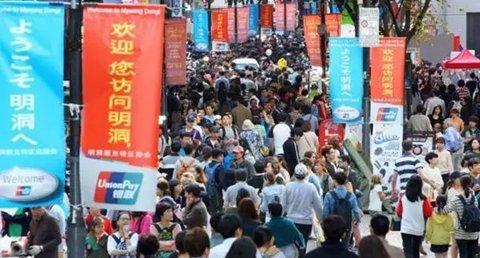 """韩国首尔著名购物区――明洞,大批中国游客在""""欢迎您访问明洞""""的横幅下购物。"""