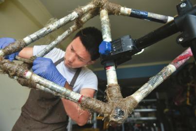 竹节在夹具上组合好后,阿布用亚麻和碳纤维结合环氧树脂将接口位置粘上。