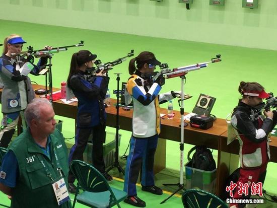 当地时间8月6日,里约奥运会首枚金牌争夺战第一枪打响,中国女子十米气手枪选手杜丽(白衣)和易思玲披挂上阵。中新网记者 宋方灿