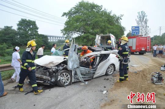 小轿车面目全非,消防官兵展开救援。 詹枭 摄
