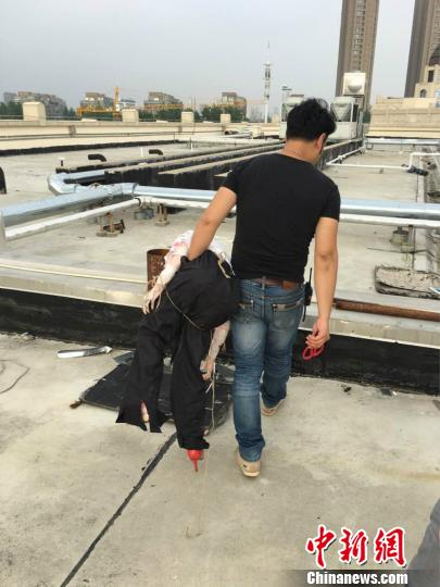 """商家现自行对楼顶停止清算,移除了使人""""恐惧""""的短发人体模子。 秦峥 摄"""