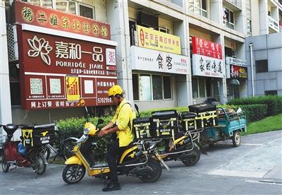 北京像素社区,北区住民楼外缀满餐馆招牌。据社区物业引见,这里百余家外卖店,9成以上都为无照运营。