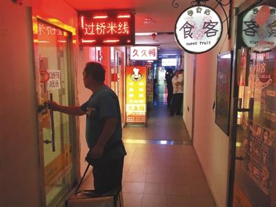 7月26日,通州区北京像素社区住民楼楼道里,麋集地开满餐馆。一位送餐员正要进门取餐。