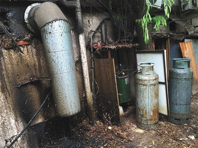 五道口啤酒花园美食城,一家餐馆厨房排烟管紧挨着煤气罐,油污直排进小树林。
