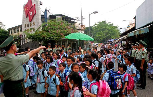 2015年7月15日,深圳,武警广东边防官兵护送跨境学童走出中英街。 视觉中国 资料图