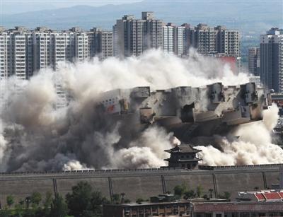 8月8日,山西大同,本地当局对位于北城墙武定西门外的一座90米高的大楼施行爆破撤除,飞腾的灰尘与古城墙照应造成壮丽局面。