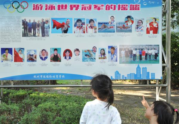 2016年8月7日,杭州陈经纶体校,参加选材班集训的小学员正在宣传板上辨认孙杨。 视觉中国 图