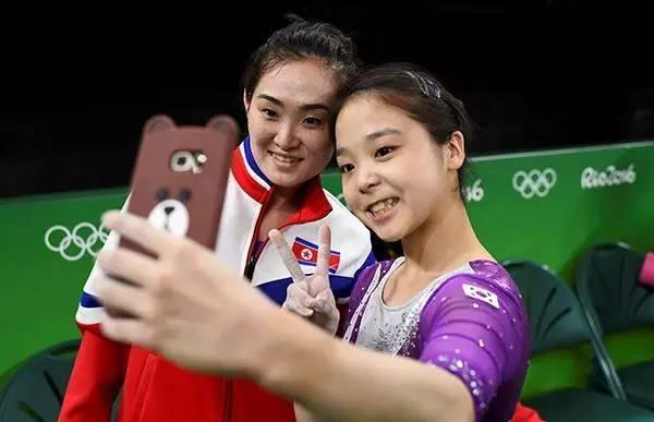 韩国体操队员李恩珠和朝鲜体操队员洪恩贞场上玩自拍。洪恩贞是08年北京奥运跳马比赛金牌得主。