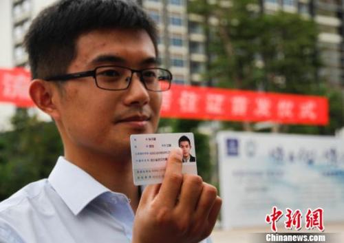 资料图。市民展示居住证。尹海明 摄