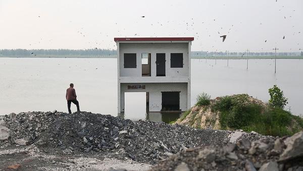 2016年7月7日,安徽淮南大李家庄,一位村民站在一座被水淹没的房子前。澎湃美色诱惑 记者 吴越 图