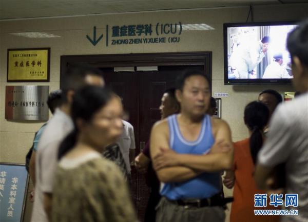 8月11日,事变受伤职员家眷在湖北当阳公民病院ICU病房门口等待。 新华社 图