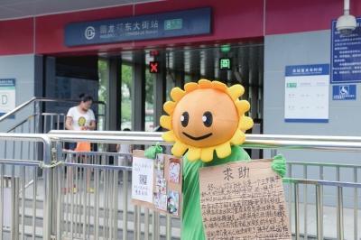 邹先生装扮成《植物大战僵尸》中的向日葵,求合影为儿子筹集医药费。京华时报记者赵思衡摄
