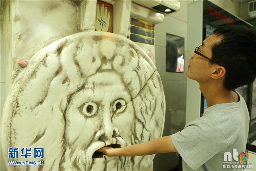 """2016年8月4日,上海。位于上海人民广场一地下商城现一台外形阴森怪异的自动""""手掌算命机""""受到年轻人欢迎,摄影师拍摄期间看到几个年轻人使用该机器算命。该机器使用说明中写着只需要投入硬币三元,将自己的手掌放在机器的特定位置,即可即时测算出自己的""""命运""""。新通图/王亚东(声明:凡带有""""ntp""""水印的图片,系新通图版权图片,受法律保护,使用(含转载)需付费,欢迎致电购买图片:010-88050891或010-88050717)"""