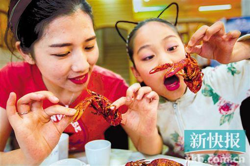 """旅客在""""龙虾之乡""""江苏省盱眙县一饭馆品味小龙虾。新华社发"""