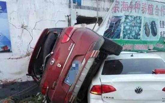 """事故现场,红色的""""长城""""牌小轿车侧翻,压着一辆白色的""""大众""""牌小轿车。"""