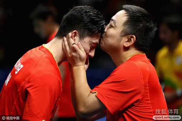 """刘国梁对亲吻马龙额头进行了解释,""""他们说这场比赛是送给我结婚十周年的礼物,我替女儿亲了下他们,这样回家就可以和女儿玩了""""。"""