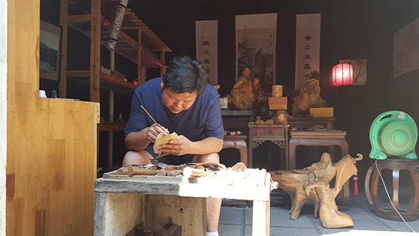 刘志华正在雕刻木雕。