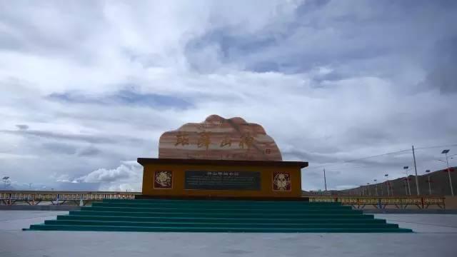 """""""神山驿站""""这四个苍劲有力,班禅大师的甘露之笔让帕羊古镇生机盎然、佛光普照、名扬四海。如果你从仲巴县出发去帕羊镇,在古镇的南边便会看到一座雕有""""神山驿站""""四字的石刻。这座石刻的石头是专门从云南运过来的,外形好似一座山,在石刻的正面还有一条类似雅鲁藏布江的青黑色天然纹络。真是巧夺天工、浑然天成!"""