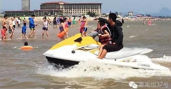 2016年8月20日,东戴河止锚湾,一名摩托艇驾驶员挥手让玩水的游客让开,而摩托艇则有一名小游客开着。