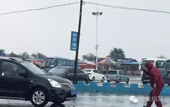 """2016年8月18日,东戴河止锚湾,男子站在车子正前方拦车""""牵驴""""(拉游客)。"""
