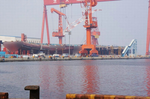 图为首艘国产航母进展曝光.-在建国产航母被巨大货轮遮挡 现场曝光