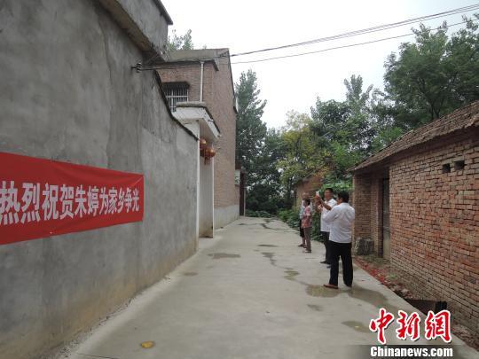 中国女排获得奥运冠军后,十里八村的乡亲们都赶来朱婷家大门外,拍张照片留作纪念。 周小云 摄