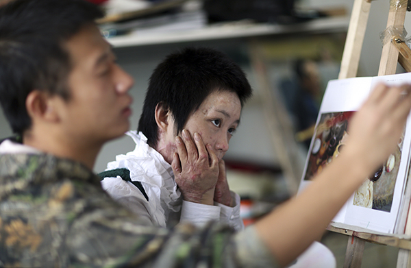 2014年10月18日,北京,绘画课上,老师为周岩改画。 视觉中国 资料图
