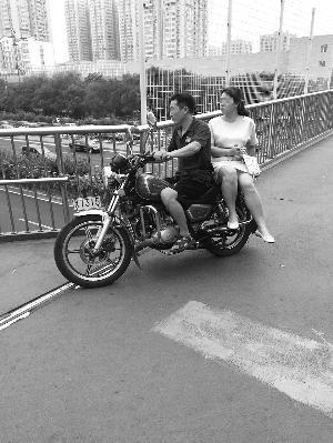 黑摩托搭载搭客间接开上过街天桥。