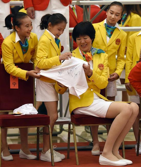 这是会见前,中国女排主教练郎平为体操运动员商春松(左二)等签名。新华社记者张铎摄