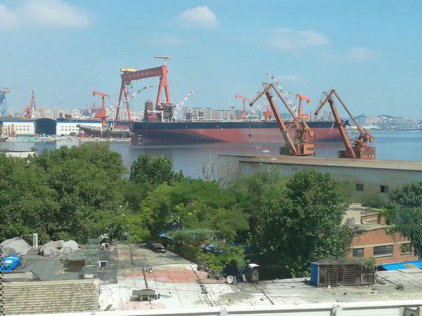 近日,网友拍摄了疑似在建首艘国产航母的最新进展,不过画面被一艘巨大的货轮挡住。