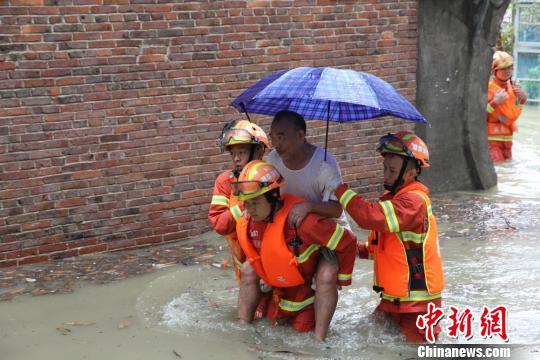 消防战士紧急转移被困居民。 侯小芳 摄