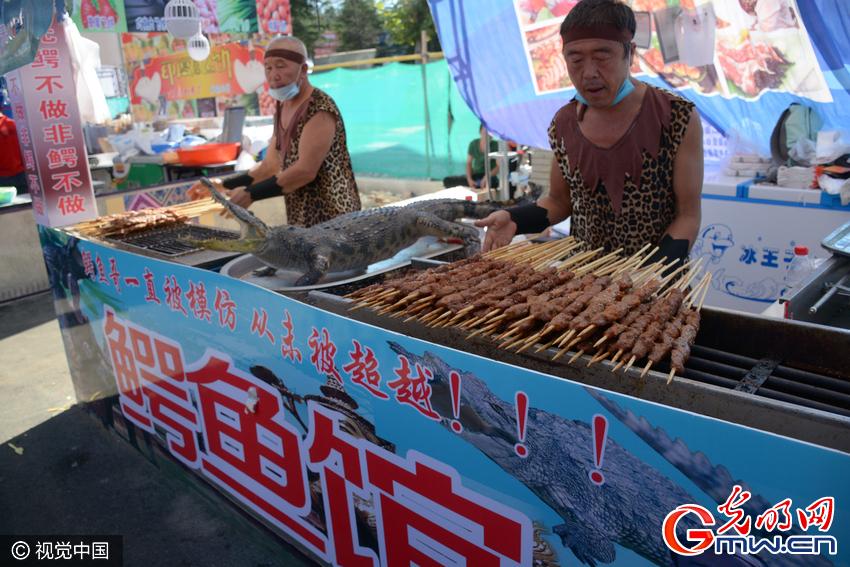 2016年8月27日,山东聊城,一条成年鳄鱼被挂在一烧烤摊上,商贩现场制作鳄鱼肉烤烧。