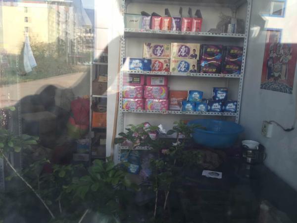 高和妻子就生活在学校内,透过小卖店窗子能看到生活用品。邵克