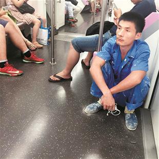楚天都市报讯 图为:蓝衣小伙蹲在地铁车厢角落里 网友拍摄