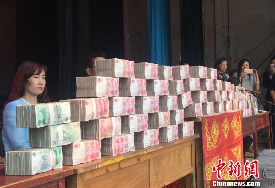 8月27日,甘肃临洮县机场村村支书边国胜现场向村里的80多户农民发放种植树苗分红。图为发放现场。 刘玉桃 摄