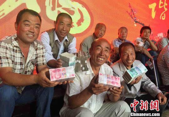 图为领到分红的村民开心坐在一起聊天。刘玉桃摄