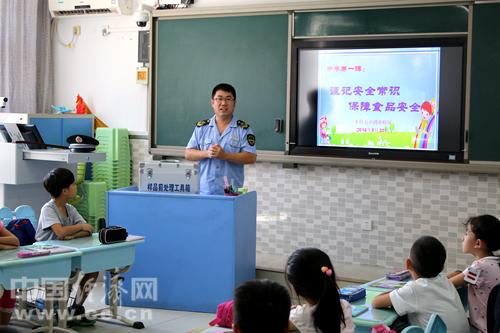 食品安全开学第一课活动现场,丰台区食药监工作人员向学生介绍食品安全知识。中国经济网记者韩肖/摄