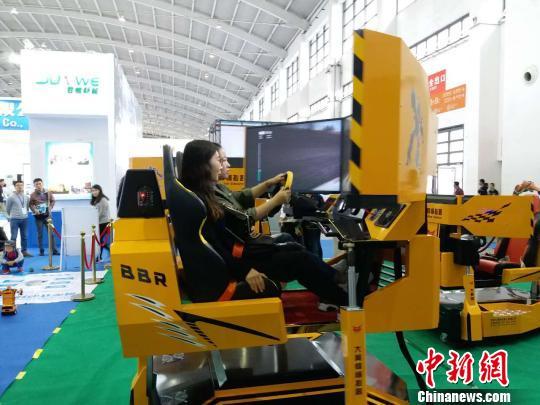 1日,在中国制博会展区,参观者被智能机器人所吸引。 张颖 摄
