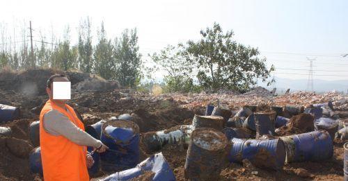 犯罪嫌疑人指认被掩埋偷排危废物。